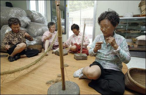 보성군 복내면 한 농가에서 할머니들이 삼 잇기 작업을 하고 있다. 허벅지에 대고 손으로 꼼꼼하게 비벼줘야 끊기지 않는다고.