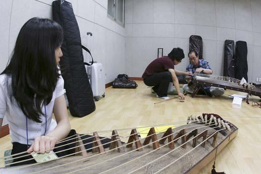 제 각각인 학생들의 악기를 손수 조율하고, 끊어진 줄을 새로 걸어주고 있는 김한승 국립국악원 정악단 예술감독
