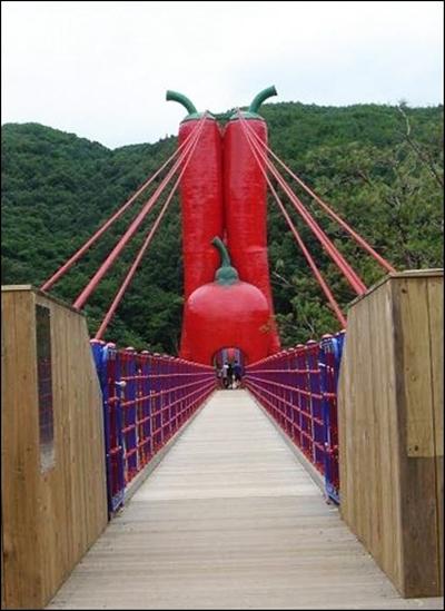 세 개의 붉은 고추 모양 탑이 인상적인  출렁다리 입구 풍경