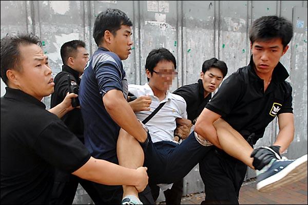 """인도안쪽에 서 있던 한 학생이 """"집시법 위반"""" 혐의로 경찰에 강제 연행되고 있다."""