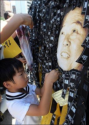 23일 오후 고 김대중 전 대통령 국장 영결식이 국회에서 열리는 가운데 서울광장 분향소에 마련된 추모의 벽에 한 어린이가 근조리본을 달고 있다.