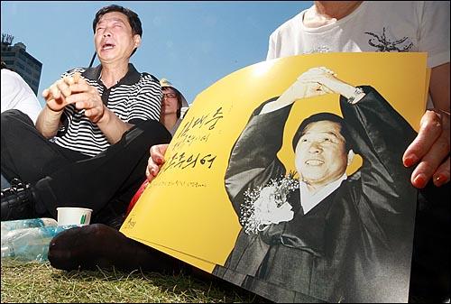 고 김대중 전 대통령의 국장 영결식이 열린 23일 오후 서울시청앞 서울광장에 마련된 고 김대중 전 대통령 분향소에서 시민들이 영결식 생중계를 시청하며 슬퍼하고 있다.