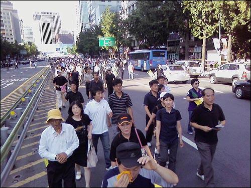 고 김대중 전 대통령을 실은 운구차가 서울광장을 벗어나자 시민들 도로로 나와 운구행렬 뒤쫓고 있다. 이를 경찰이 가로막는 등 과도하게 통제해 시민과 충돌 일어나기도 했다. 일부 구간에서는 차량통제가 전혀 없어 시민과 차가 뒤섞이기도 했다. (휴대전화 '9246'님이 엄지뉴스 #5505로 보내주신 사진입니다.)