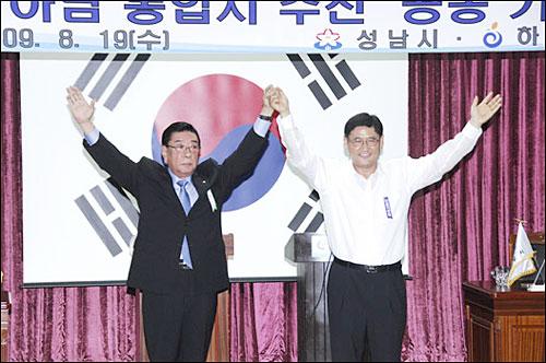 이대엽 성남시장(사진왼쪽)과 김황식 하남시장이 지난 19일 성남시청 대회의실에서 기자회견을 열어 두 자치단체의 통합을 발표하고, 합의문에 서명한 뒤 두 손을 들어 포즈를 취하고 있다.