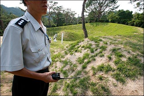 15일 오후 서울 동작구 국립현충원내 고 김대중 전 대통령 묘소에서 무전기를 든 경비원들이 묘지 훼손을 막기 위해 경비를 서고 있다.