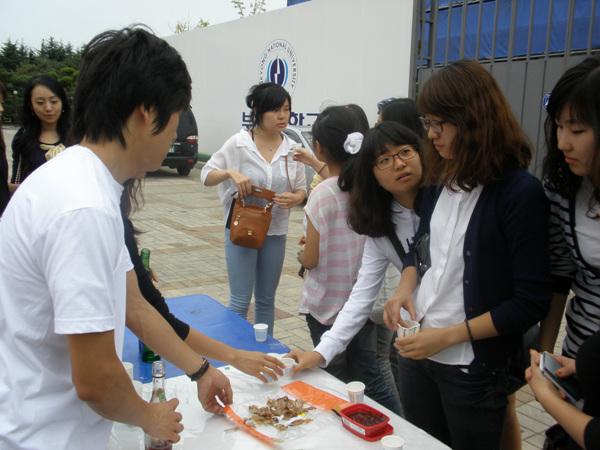 시음대회  '들쭉술과 평양소주'를 맞보려고 줄서있는 모여 있는 학생들