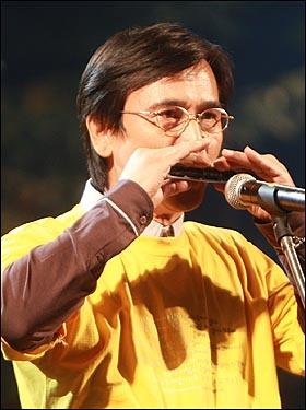 유시민 전 보건복지부 장관이 9일 저녁 서울 구로구 성공회대학교 운동장에서 열린 '노무현재단 출범기념 콘서트-파워 투 더 피플(Power to the People)'에서 하모니카로 '행복의 나라'를 연주하고 있다.