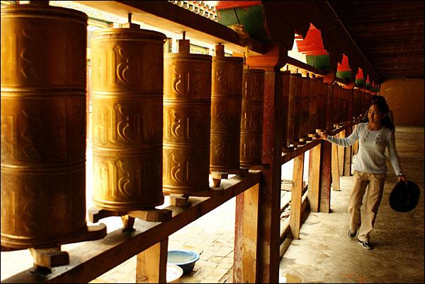 마니통을 돌리는 티베트 소녀. 티베트인은 마니통을 한 바뀌 돌릴 때마다 죄업이 하나씩 사라진다고 믿고 있다.