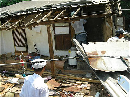공사 시작, 낡은 집을 조심조심 헐어내고 있습니다.