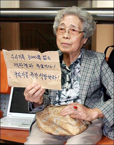 28일 오후 서초동 서울중앙지법에서 열린 용산철거민 참사 선고공판에서 기소된 철거민 농성자 9명중 7명에게 징역 5~6년의 중형이 선고된 가운데, 한 방청객이 법원 로비에서 '수사기록 3,000쪽 없는 재판결과 무효이다. 구속자를 즉각 석방하라'는 손피켓을 들고 있다.
