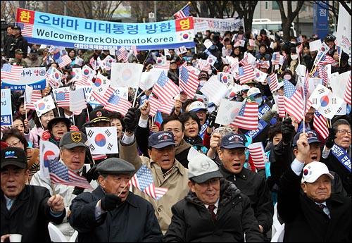 한미정상회담이 예정된 19일 오전 서울 세종로네거리에서 애국단체총협의회 주최로 열린 '오바마 미 대통령 방한 환영대회'에서 참석자들이 성조기와 태극기를 흔들고 있다.