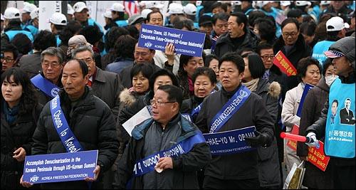 한미정상회담이 예정된 19일 오전 서울 세종로 미대사관 부근에서 'SA-RANG-HAE-YO Mr. OBAMA' 'Welcome Obama to Korea' 등이 적힌 손피켓을 든  자유총연맹 회원 수백명이 오바마 미 대통령을 태운 차량 행렬을 환영하기 위해 이동하고 있다.