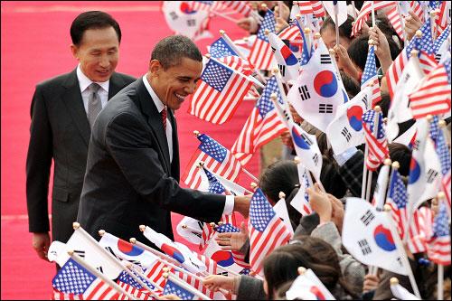 11월 19일 청와대에서 열린 공식환영식에서 이명박 대통령과 버락 오바마 미국 대통령이 태극기와 성조기를 흔들며 환영하는 어린이들과 인사하고 있다.