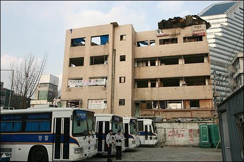 용산철거민참사가 발생한지 1년이 되어 가는 가운데 22일 오후 참사 현장인 서울 한강로 남일당 빌딩앞에 경찰과 호송버스 여러대가 대기하고 있다.