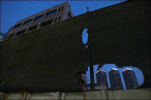 22일 오후 용산철거민참사 현장인 서울 한강로 남일당 빌딩의 가림막 사이로 재개발로 완성된 고층아파트가 불을 밝히고 있다.