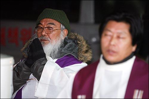 용산철거민참사가 발생한지 337일째를 맞이한 22일 저녁 서울 한강로 남일당 빌딩앞에서 열린 천주교정의구현사제단 생명평화미사에서 문정현 신부가 손모아 기도를 하고 있다.
