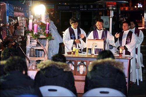 용산철거민참사가 발생한지 337일째를 맞이한 22일 저녁 서울 한강로 남일당 빌딩앞에서 유가족과 시민들이 참석한 가운데 천주교정의구현사제단 생명평화미사가 열리고 있다.