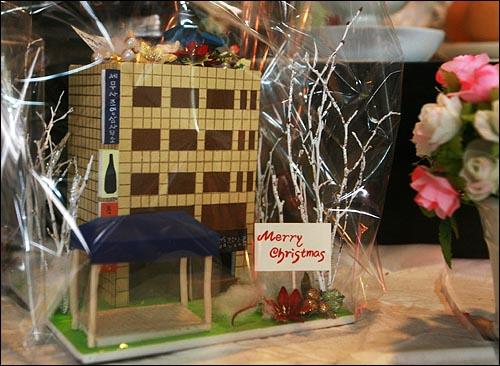 크리스마스를 몇일 앞둔 22일 오후 용산철거민참사 현장인 용산구 한강로 남일당 건물 1층 합동분향소에 크리스마스 장식으로 꾸며진 남일당 건물과 농성천막 모형이 정성스럽게 포장된 채 놓여 있다.