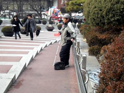한 시각장애인이 명동성당 입구에서 구걸하고 있다.