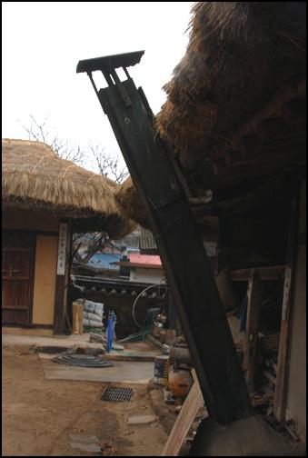 굴뚝 대문채 뒤편에 서 있는 판자로 만든 굴뚝. 고향 집에 온것 같은 푸근함을 느끼게 만든다.