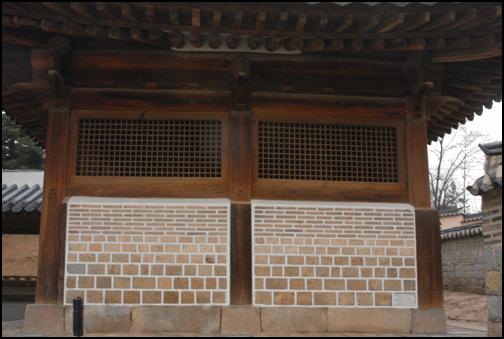 화령전의 벽 격자창을 내고 그 밑에 벽돌을 쌓아올린 담벼락. 돌의 크기가 위로 올라갈 수록 작아져 멋을 더한다.