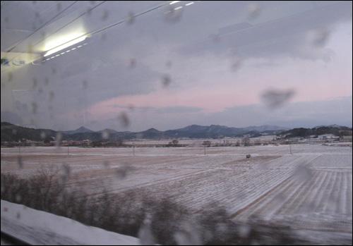 열차 차창 밖으로 펼쳐진 농촌 들녘 풍경.
