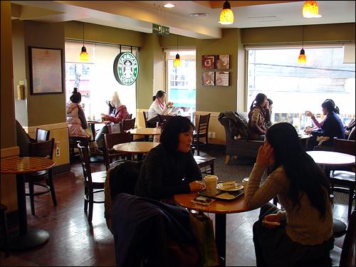 스타벅스 매장 사람들이 모여 커피를 마시고 있다