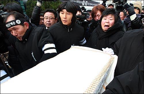 용산참사 희생자들의 장례식이 참사 발생 355일 만에 거행된 9일 오전 서울 한남동 순천향병원에서 열린 발인식에서 영정을 앞세운 시신이 운구차로 옮겨지자 고 이성수씨 부인 권명숙씨가 오열하고 있다.