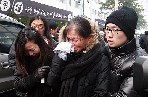 용산참사 희생자들의 장례식이 참사 발생 355일 만에 거행된 9일 오전 서울 한남동 순천향병원에서 열린 발인식에서 영정을 앞세운 시신이 운구차로 옮겨지자 고 한대성씨 부인 신숙자씨가 오열하고 있다.