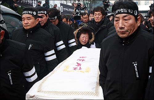 용산참사 희생자들의 장례식이 참사 발생 355일 만에 거행된 9일 오전 서울 한남동 순천향병원에서 열린 발인식에서 영정을 앞세운 시신이 운구차로 옮겨지자 고 양회성씨 부인 김영덕씨가 오열하고 있다.
