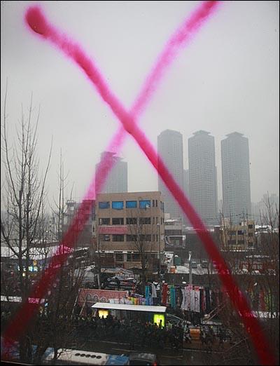 용산참사 희생자들의 장례식이 참사 발생 355일 만에 거행된 9일 오후 서울 한강로 남일당 참사현장 앞 재개발 공가에서 노재를 하기 위해 도착한 운구행렬이 보이고 있다.