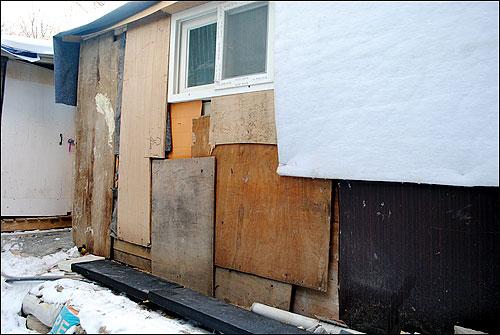 서초동 산청마을 판자촌에 있는 집. 벽이 허물어져 합판으로 덧대었기 때문에 겨울이면 찬바람이 틈새로 스며들어 애를 먹는다.