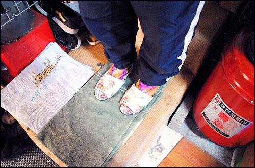 서초동 산청마을에 사는 한 주민. 실내에 있지만, 난방이 되지 않아 항상 두꺼운 덧신과 신발을 신고 생활한다.