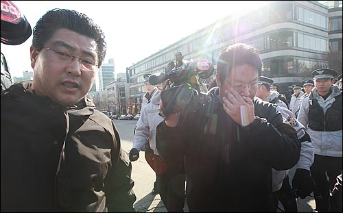 21일 오후 서초동 서울중앙지법 앞에서 열린 '이용훈 대법원장과 문성관 판사 사퇴 촉구 기자회견' 중 MBC 카메라 기자가 보수단체 회원으로부터 뿌려진 휘발유를 닦아내고 있다.