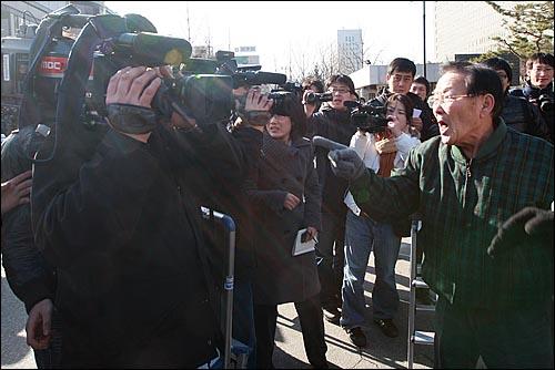 21일 오후 서초동 서울중앙지법 앞에서 열린 '이용훈 대법원장과 문성관 판사 사퇴촉구 기자회견' 중 보수단체 회원들이 MBC 'PD수첩' 무죄판결에 항의하며 MBC 카메라 기자에게 욕설을 퍼붓고 있다.