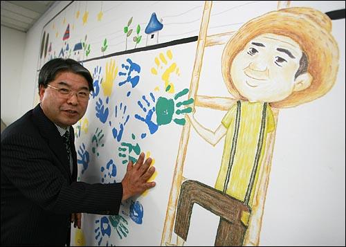 이재정 국민참여당 대표가 28일 오후 고 노무현 전 대통령 그림과 함께 마포구 당사 사무실 벽에 찍혀 있는 당원들의 손바닥 자국에 자신의 손을 대보고 있다.