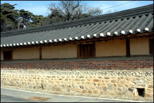 바깥담벼락 대문 좌우에 마련한 행랑채의 담벼락이 외벽이다. 벽돌과 기와, 돌을 이용해 쌓은 문양이 특이하다.
