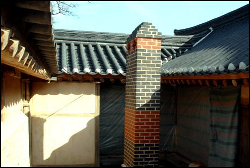 굴뚝 사랑채 뒤편의 굴뚝. 검은 벽돌과 붉은 벽돌을 사용해  무게를 내고 있다.