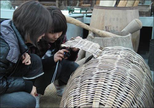 슬비와 예슬이가 옛 닭장을 살펴보며 카메라에 담고 있다.