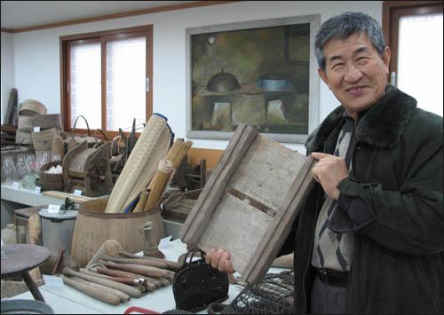 김성우 와보랑께박물관장이 전시실에서 옛 썰매를 들어보이며 웃고 있다.