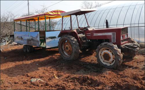 팔방미인마을을 찾는 체험객들이 타고 이동하는 트랙터. 비수기인 요즘 트랙터가 황토밭에서 쉬고 있다.