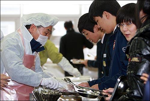 이재오 국민권익위원장이 11일 정오 서울 용산구 중경고등학교를 찾아 학교급식 관련 제도개선을 확인한 뒤 학생들에게 배식을 하고 있다.