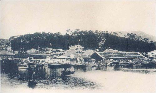 부산 영사관  바다에서 바라본 부산영사관. 중앙의 깃대 있는 뒤쪽 높은 건물이 영사관이다. 뒤편으로 보이는 숲이 현재 용두산 공원.