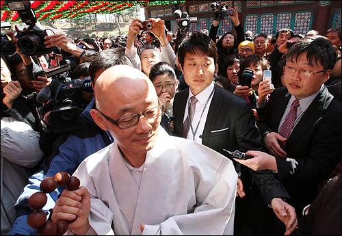 봉은사 주지 명진스님이 28일 오전 서울 삼성동 봉은사에서 법회를 마친 뒤 신도들과 취재진에 둘러싸인 채 법왕루를 나서고 있다.