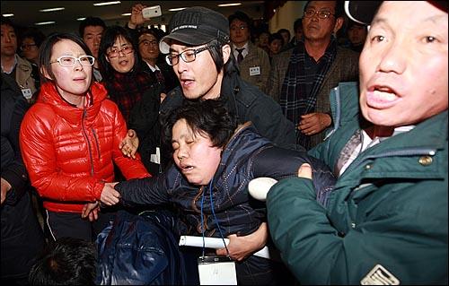 해군 초계함 '천안함' 침몰 나흘째인 29일 오후 경기도 평택 해군 제2함대에서 실종자 가족 한 명이 실신해 부축을 받으며 실려 나가고 있다.