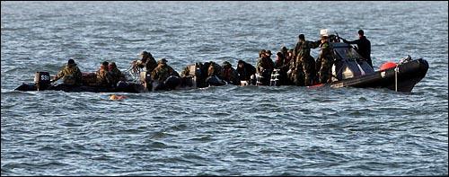 3일 오후 천안함이 침몰한 백령도 사고 해역 함미 부분에서 실종자 남기훈 상사의 시신이 발견된 직후 구조대원들이 시신을 실은 보트(오른쪽)에서 시신을 수습하고 있다. (사진공동취재단)