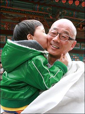 11일 낮 서울 삼성동 봉은사 법왕루에서 일요법회를 마치고 나오는 명진 스님에게 한 어린이가  뺨에 입을 맞추고 있다.