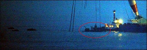 해군 초계함 '천안함' 침몰 18일째인 12일 저녁 함미 침몰해역에서 작업중이던 대형크레인이 함미부분에 쇠사슬 2개 결색을 완료한뒤 수심이 낮은곳에서 정박해 있다.