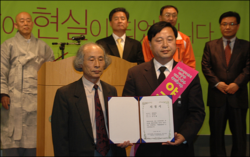 김두관 전 행정자치부 장관이 안승욱 희망자치만들기경남연대 공동대표로부터 '야권단일후보 지정서'를 받은 뒤 들어보이고 있다.