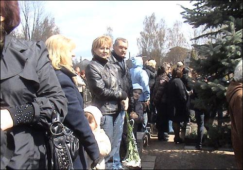 손에 꽃을 든 조문객들이 케디스의 장례식에 모여들었다.
